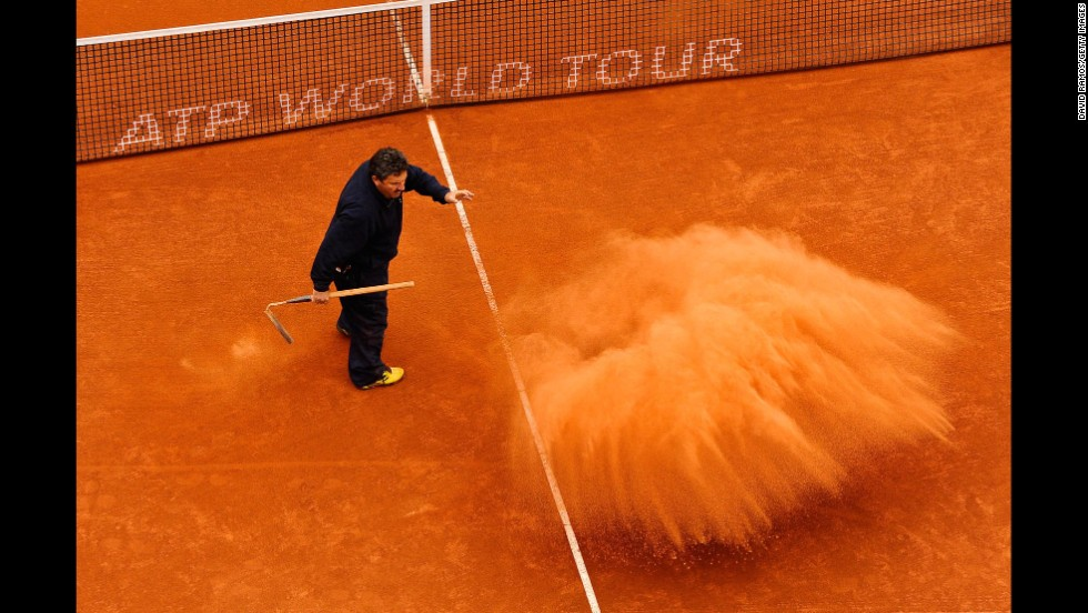 A staff member throws clay on the court during the final match on day seven of the 2013 Barcelona Open Banc Sabadell on April 28 in Barcelona. Rafael Nadal won 6-3, 6-4.