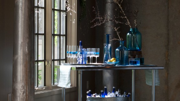 A sleek metal bar cart with blue glassware fits a modern or traditionally decorated space.