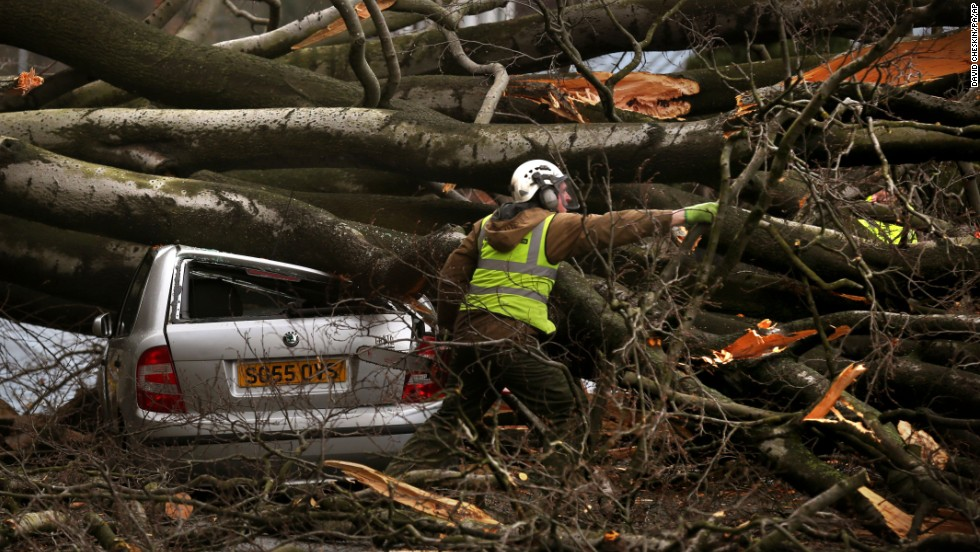 A man works to remove a tree that was blown over by the wind December 5, in Edinburgh, Scotland.