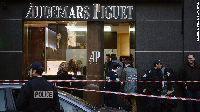 French policemen stand guard in front of a jewellery store that was attacked on December 5, 2013, in Paris.