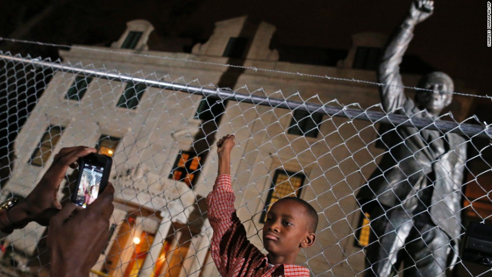 Keaton Anderson, 10, poses for a photograph while he and his father visit Mandela's statue at the South African Embassy in Washington on December 5. The statue is under renovation.