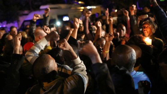 South Africans pay tribute to Mandela in Johannesburg following his death December 5.