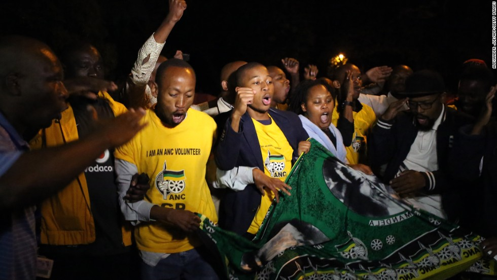 South Africans sing as they pay tribute to Mandela in Johannesburg on December 5.