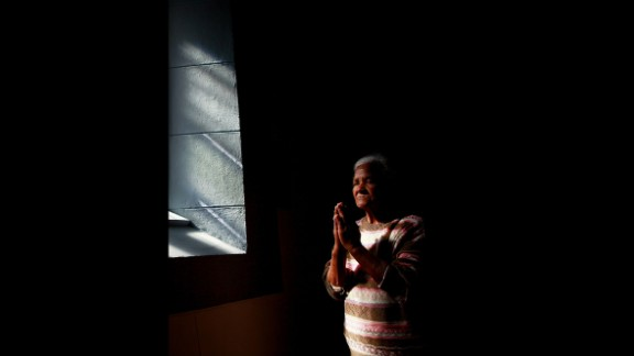 A woman prays at the Central Methodist Church as people remember Mandela on Friday, December 6, in Cape Town, South Africa.