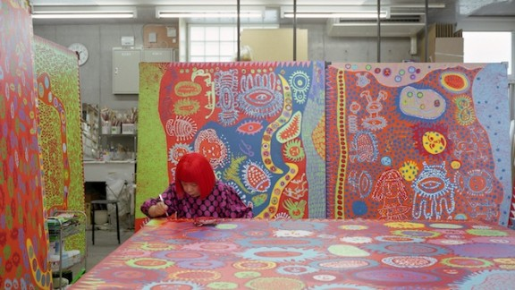 here Kusama is pictured working in her studio. The artist says the kaleidoscopic rooms are her attempt to investigate life, death and infinity.
