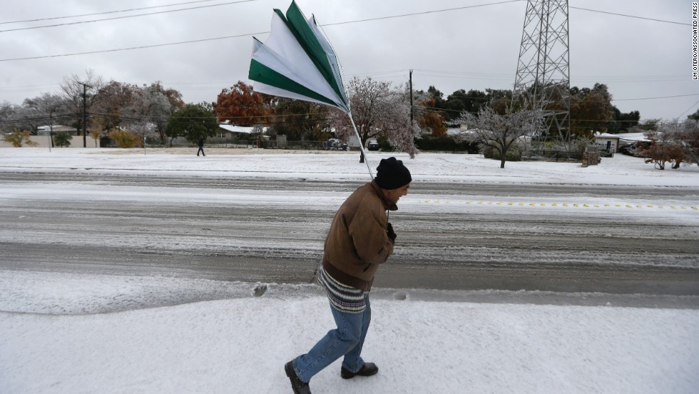 A gust of wind collapses Joseph Mezo's umbrella as he walks to work on December 6 in light sleet and ice conditions in Dallas.