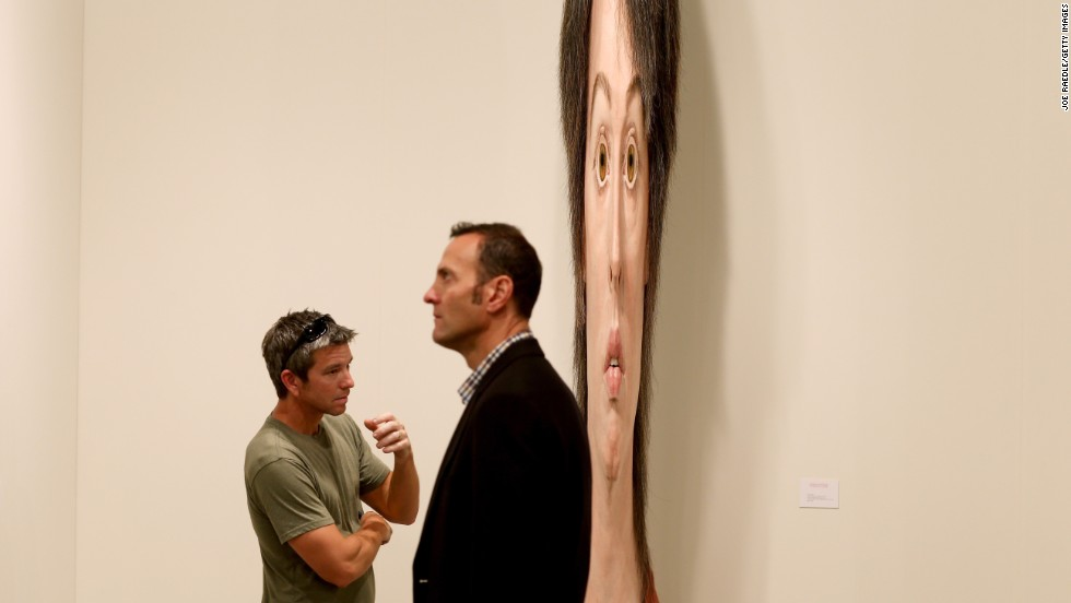 "Lance Vickery, left, looks at a work by Evan Penny titled ""female stretch variation # 2"" on December 5."