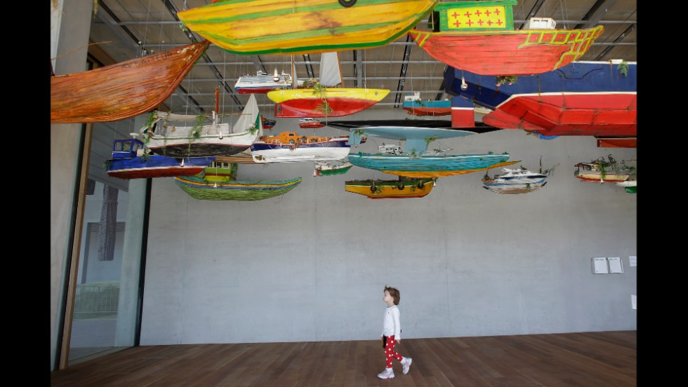 "Ava Crowley, 4, of Miami, walks among an installation of boats by the artist Hew Locke titled ""For Those in Peril on the Sea"" at the Perez Art Museum Miami on December 7."