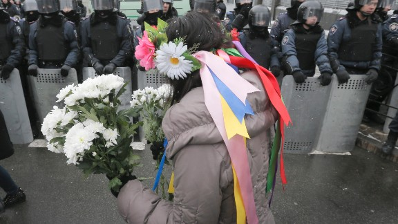 A pro-EU activist offers flowers to police officers at the presidential office in Kiev on December 8.