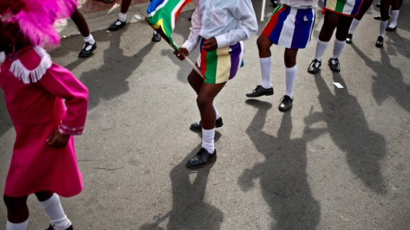 Children in a drum majors group perform a dance outside Mandela's old house on Saturday, December 7.