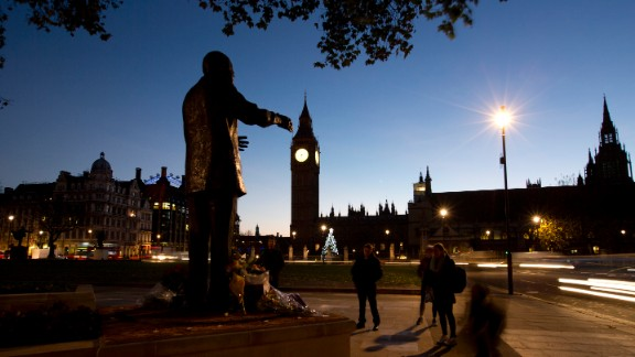 Early morning commuters stand in silence beside a statue of Mandela on December 6 in Parliament Square in London.