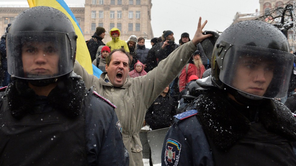 A protester shouts behind riot police standing guard in Independence Square on December 9.