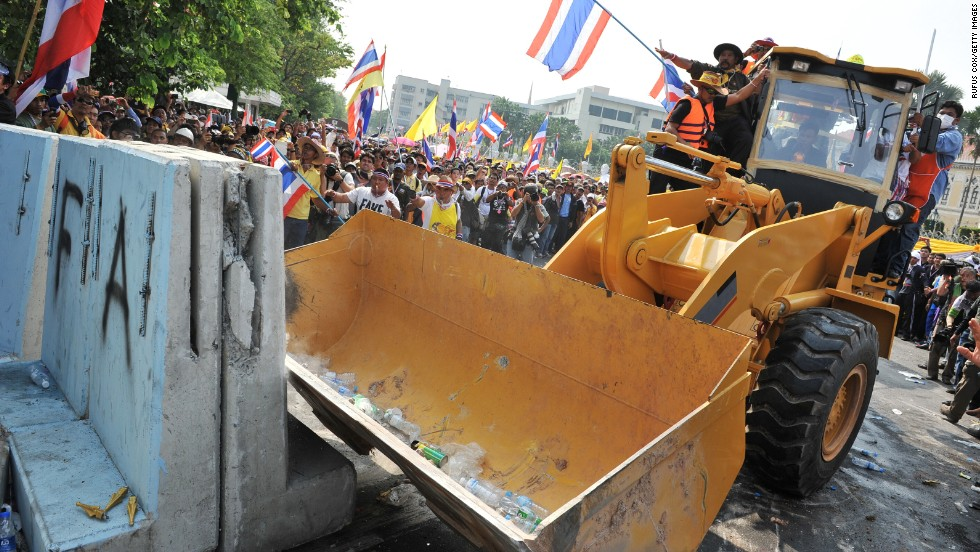 Protesters use a bulldozzer to clear a police barricade blocking an access road leading to Government House during a large anti-government rally on December 9.