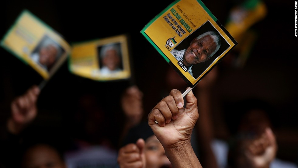 Mourners wave flags at a telecast of the memorial service at Ellis Park in Johannesburg.