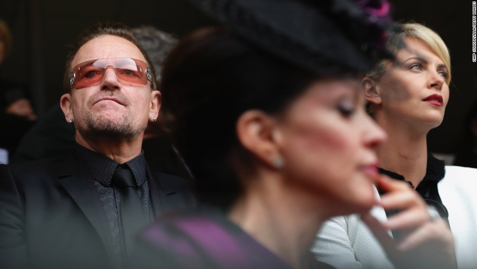 Singer Bono and actress Charlize Theron attend the memorial service.