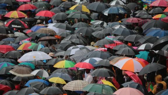 People take shelter under umbrellas at FNB Stadium.