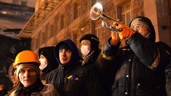 A man plays a trumpet as he call protesters to be ready for police attack at Kiev's City Hall on December 10, 2013.