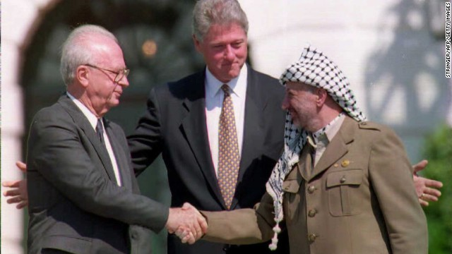 U.S. President Bill Clinton stands between PLO leader Yasser Arafat and Israeli Prime Minister Yitzahk Rabin as the two shake hands on October 25, 1995.   Rabin and Arafat shook hands for the first time after Israel and the PLO signed a historic agreement on Palestinian autonomy in the occupied territories.