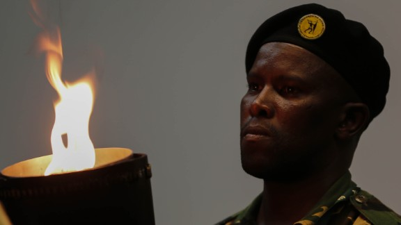 A South African soldier watches the flame of the torch before entering the field during the memorial service.