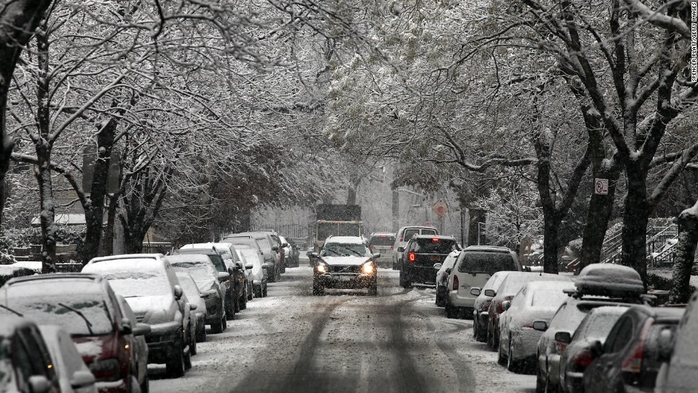 A car drives up a snow-covered street in Brooklyn, New York, on December 10.