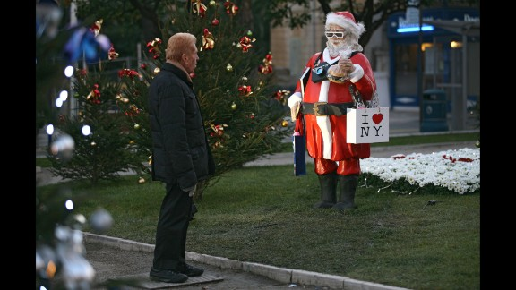 """A man checks out a statue called """"Santa Claus Tourist in the USA"""" in Menton, France, on December 9."""