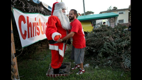 Anthony Martinez, owner of a Miami Christmas tree lot, adjusts the outfit on a