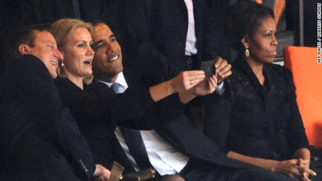 "Despite apparent disapproval from the First Lady, Obama poses for a selfie with the Danish PM, known as ""Gucci Helle"" for her love of designer clothes, and her British counterpart David Cameron."