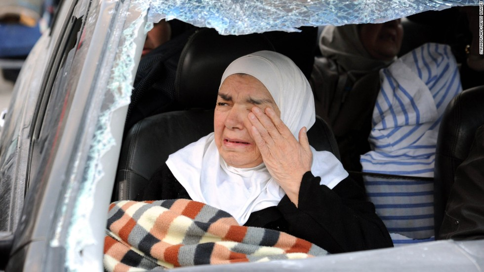 A woman weeps inside a damaged vehicle after forces loyal to President Bashar al-Assad captured the town of Nabak on Monday, December 9.