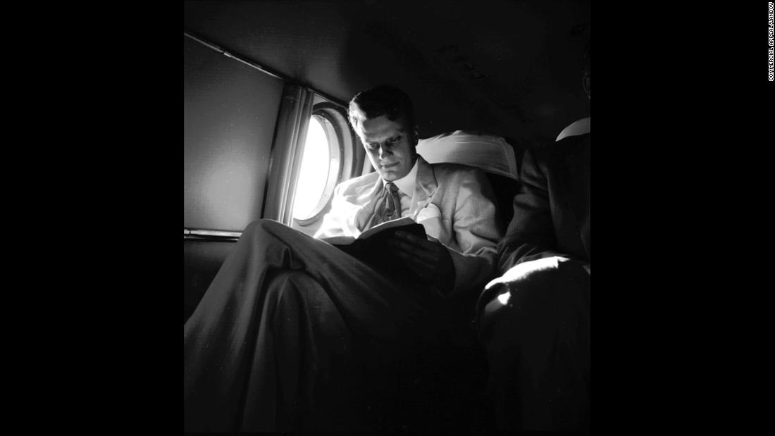 "Graham reads on an airplane during a ""Pulpit in the Sky"" trip in 1953."