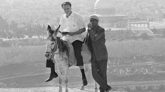 Graham rides a donkey in Jerusalem while visiting the city in 1969.