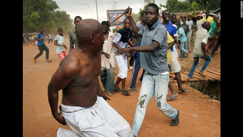 <strong>December 9:</strong> A Christian man chases a suspected Seleka officer in civilian clothes with a knife near the airport in Bangui, Central African Republic. The Seleka man was taken into custody by French forces, who fired warning shots to disperse the crowds. The Central African Republic is in the midst of a bloody civil war between various proclaimed Christian and Muslim militias and other rebel factions.
