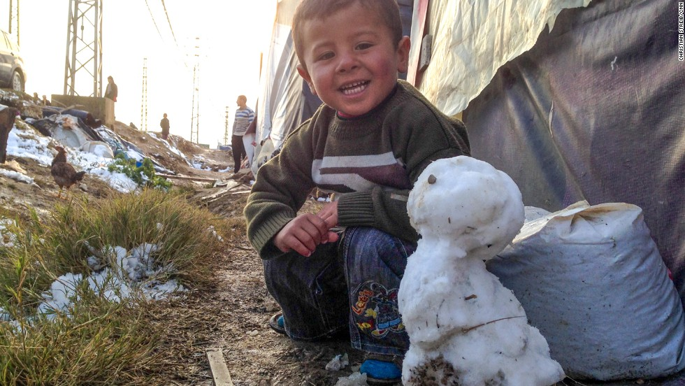 A Syrian boy shows off his snowman at a refugee camp in the Bekaa Valley on December 12.