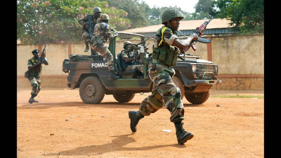 Peacekeeping troops from the Multinational Force of Central Africa shoot as they attempt to evacuate Muslim clerics from the St. Jacques Church in Bangui on Thursday, December 12. An angry crowd had gathered outside the church following rumors that a Seleka general was inside.