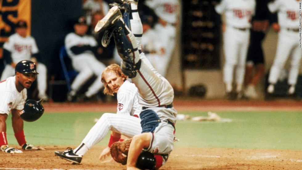 Dan Gladden of the Minnesota Twins looks back after colliding with the Atlanta Braves catcher at home plate during a 1991 World Series game in Minneapolis.