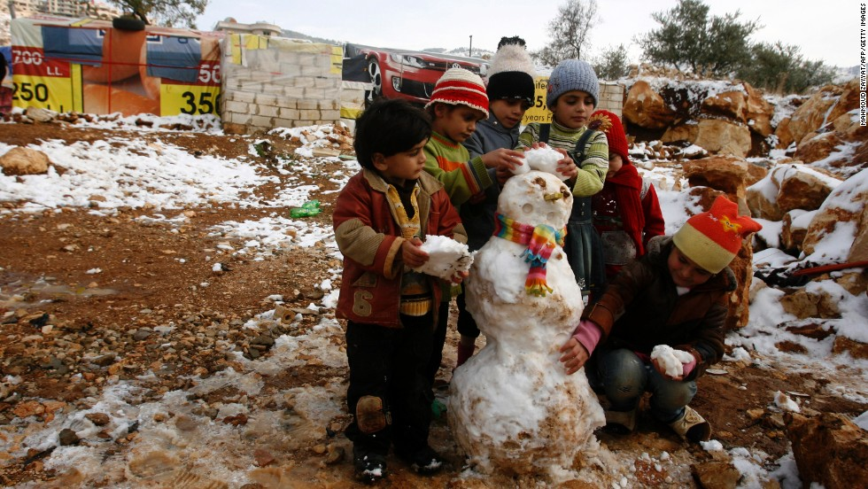 Young Syrian refugees build a snowman following a storm in the Lebanese village of Baaloul on Thursday, December 12.