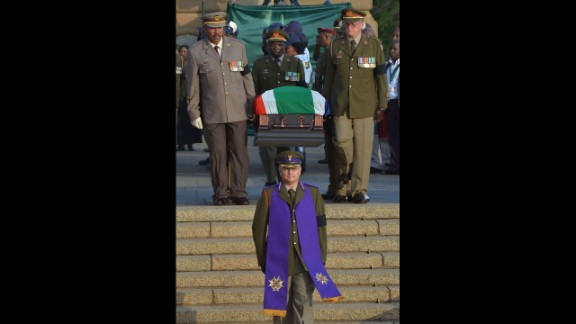 The national flag-draped coffin of the former South African President is carried down steps of the Union Buildings at the end of the third and final day of lying in state on December 13.