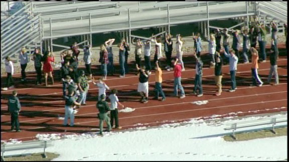 Persons evacuated from Arapahoe High School in Centenial, Colorado, walk on the school
