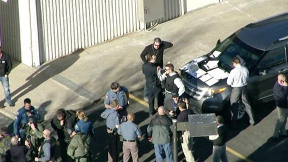 Law enforcement personnel gather near the high school.