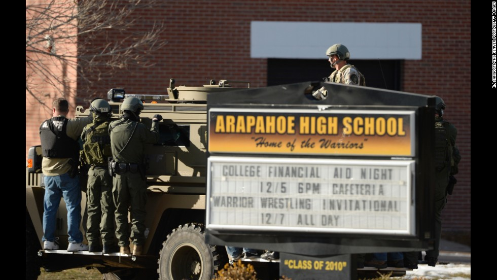 Law enforcement personnel arrive at the high school in a military-style vehicle.