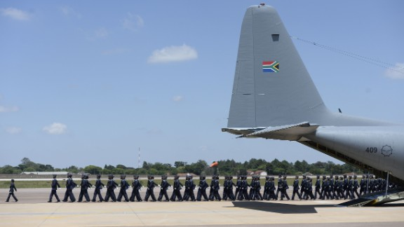 Troops march near the plane that transported Mandela