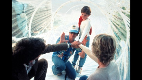 """Spielberg, wearing a hat, works with actors Peter Coyote, Henry Thomas and Dee Wallace during the filming of """"E.T.; The Extra-Terrestrial"""" in 1982. As of 2013, the movie had made more than $792 million worldwide."""