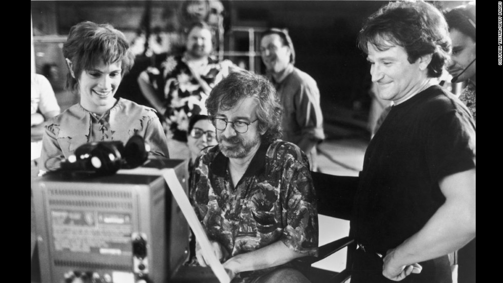 "Actors Julia Roberts and Robin Williams watch production footage with Spielberg on the set of the film ""Hook"" in 1991."