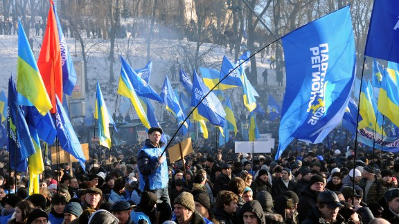 Supporters of the president wave flags of the ruling Party of Regions, as well as Ukrainian flags, during a rally on Kiev