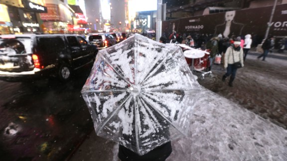 A woman uses an umbrella to protect herself from snow on December 14 in New York's Times Square.