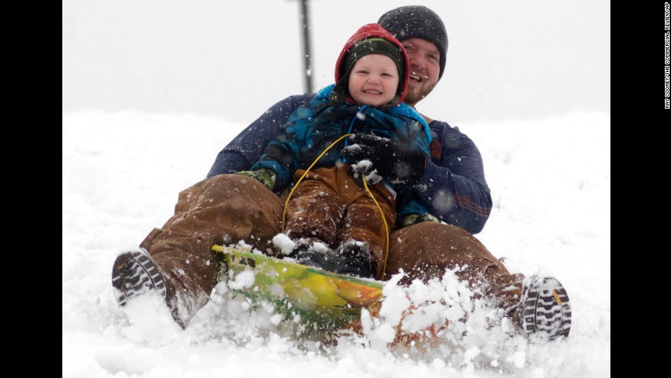 Cooper Reynolds, 3, grins as he sleds down a hill with his father, Ronnie Reynolds, on December 14 at Hudson Family Park in Portland, Indiana.