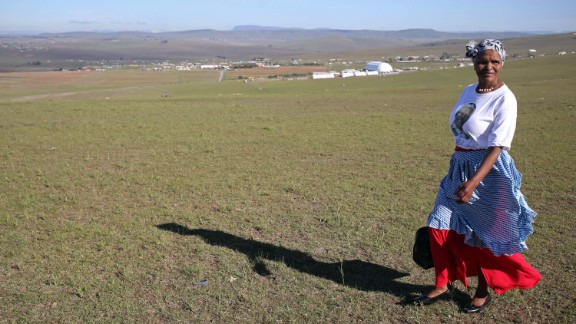 A woman walks on a hill overlooking the processional to Mandela
