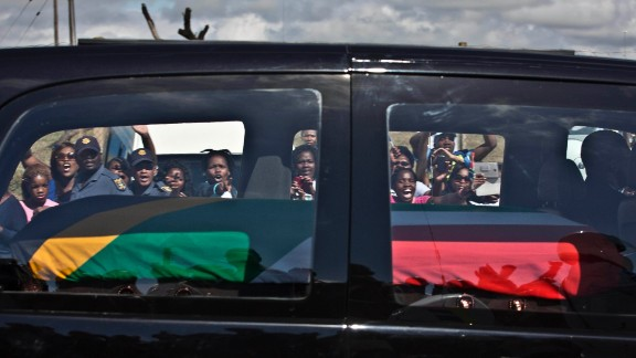 Mourners wave and cheer as the hearse carrying Mandela
