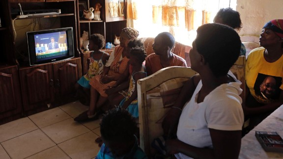 A family watches the funeral service from their home in Soweto, South Africa.