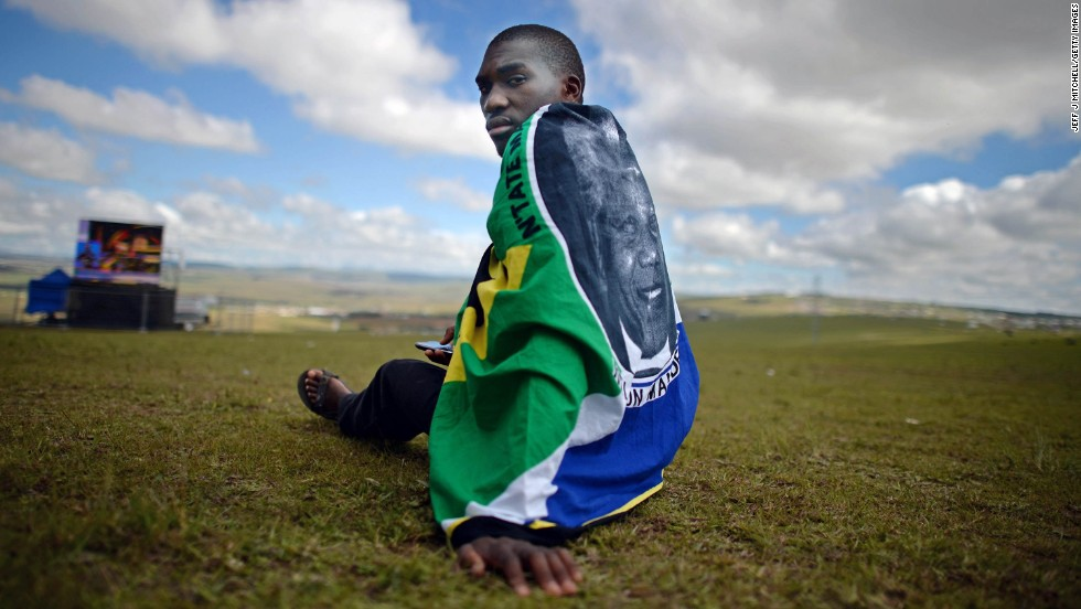 A man sits on a hill as the ceremony is broadcast on huge screens at Mandela's burial site in Qunu.
