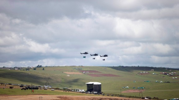 Three helicopters fly over the grave site of former South African President Nelson Mandela as his family lays his body to rest in his hometown of Qunu, South Africa, on Sunday December 15. Mandela